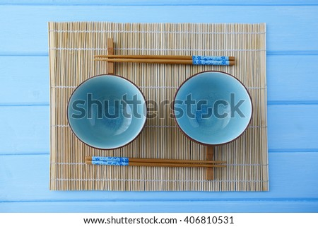 Empty plate and sushi chopsticks on wood blue table - stock photo