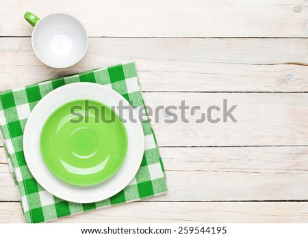 Empty plate, cup and towel over wooden table background. View from above with copy space - stock photo