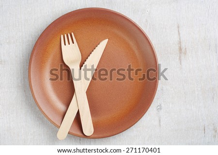 Empty plate, fork and table knife on old table, top view - stock photo