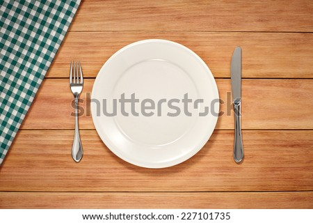 Empty Plate, Fork, Knife and Table Cloth on wooden background. Top View with Text Space - stock photo