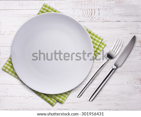 Empty plate, knife, fork and towel over wooden table background. View from top with copy space. - stock photo