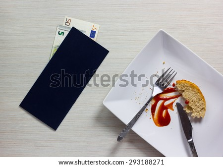 Empty plate left after dinner with bill and Euro note on wooden table - stock photo