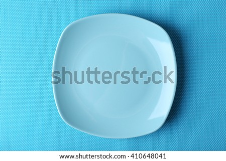 Empty plate on blue textured mat background - stock photo