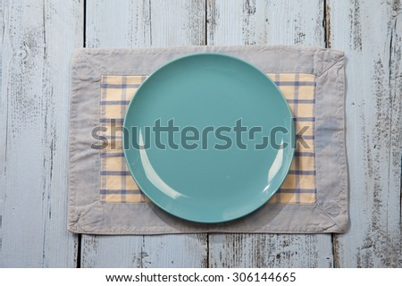 Empty plate on light blue wooden background - stock photo