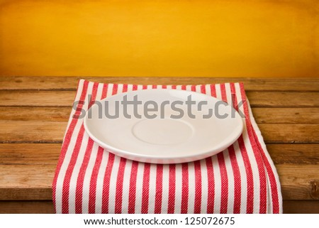 Empty plate on tablecloth over grunge yellow background - stock photo