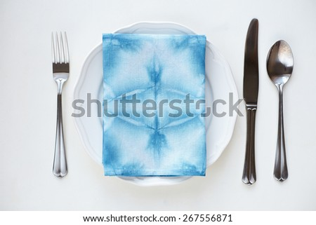 Empty plate on tabletop with tablecloth close up - stock photo