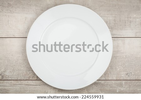 empty plate on wood table - stock photo