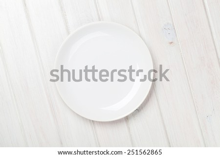 Empty plate over white wooden table background with copy space - stock photo