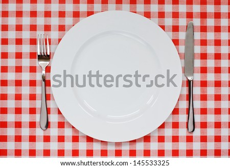Empty plate setting with plate, knife and fork on red gingham background popular symbol for diners and cafes - stock photo
