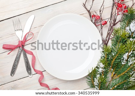Empty plate, silverware and christmas tree. View from above over white wooden table background - stock photo