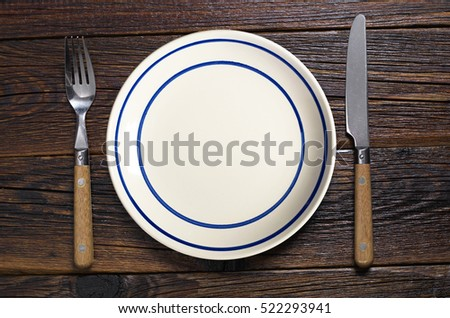 Empty plate with blue stripe and cutlery on dark wooden table, top view