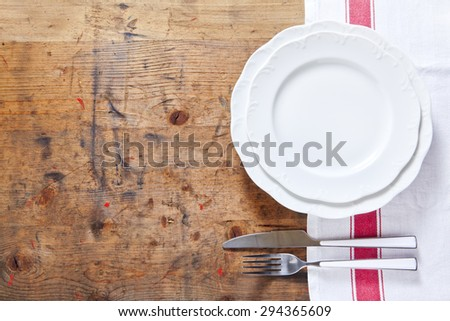 empty plate with cutlery on a wooden background. space for writing or placing text menu. background for restaurants - stock photo