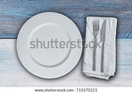 Empty plate with cutlery on blue and white  wood.