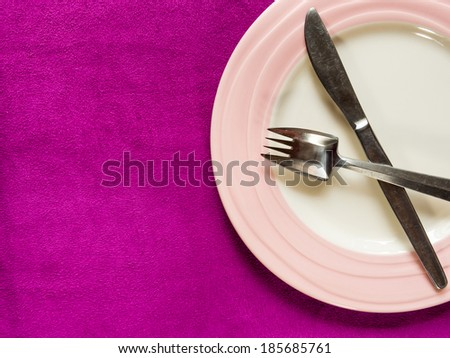 Empty Plate with fork and knife on purple background