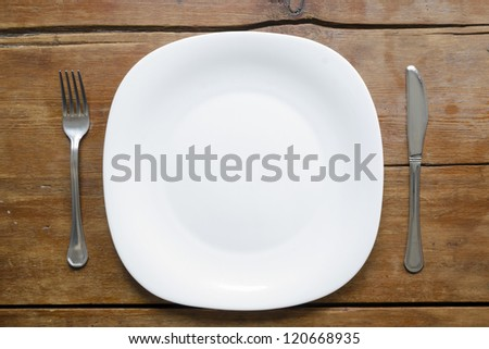 empty plate with fork and knife on the vintage wooden table - stock photo