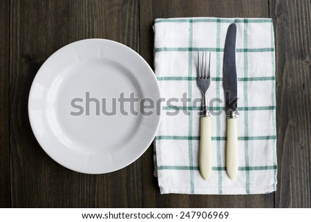 Empty plate with fork and knife on wooden table - stock photo