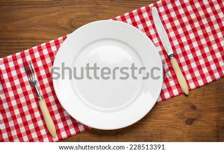 Empty plate with fork and knife on wooden table. Table arrangement.