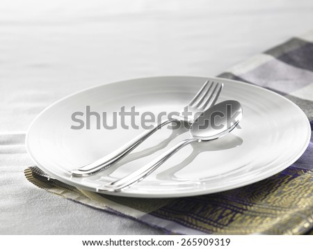 empty plate with fork and spoon - stock photo