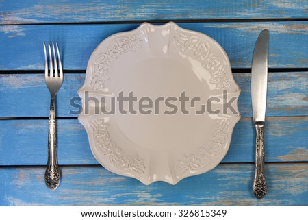 empty plate with  knife and fork on colorful wooden table - stock photo