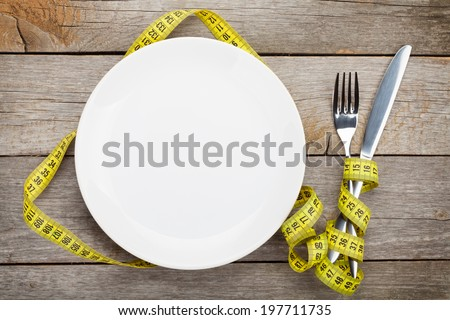 Empty plate with measure tape, knife and fork. Diet food on wooden table - stock photo