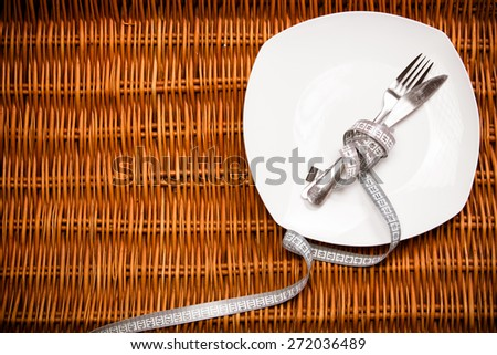 Empty plate with measure tape, knife and fork. Diet food on wooden table.Fitness concept with healthy dieting.Healthy lifestyle concept, diet and fitness - stock photo