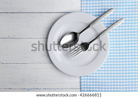 Empty plate with silver cutlery on wooden background - stock photo