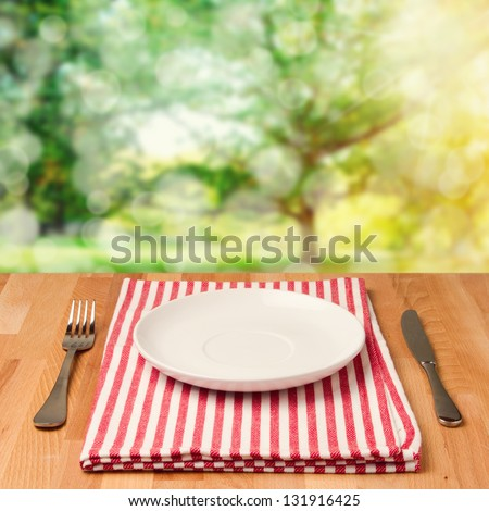 Empty plate with silverware on wooden table over bokeh background - stock photo