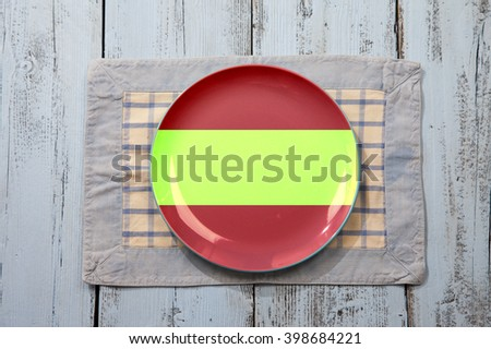 Empty plate with Spanish flag on light blue wooden background - stock photo