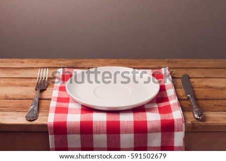 Empty plate with tablecloth and silverware on wooden table