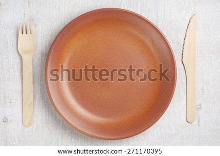 Empty plate, wooden fork and table knife on rustic table, top view - stock photo