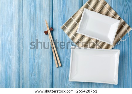 Empty plates and chopsticks on blue wooden background. Top view with copy space - stock photo