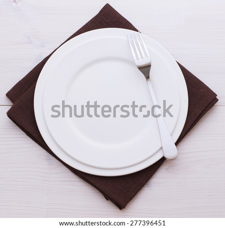 Empty plates and cutlery on table cloth on wooden table for dinner. Top view square. Flat mock up for design.