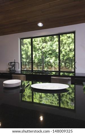 Empty plates on black gloss kitchen worktop - stock photo