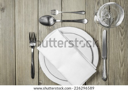 Empty plates with a napkin dining room, cutlery set and empty wine glass on a wooden background - stock photo