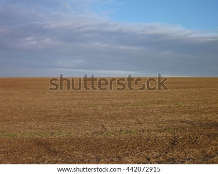 Empty ploughed field with brown soil - stock photo