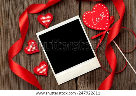 Empty polaroid photo frame with red hearts and ribbons for valentine's day on wooden background  - stock photo
