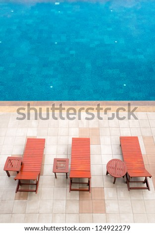 empty poolside deckchairs with beautiful blue swimming pool - stock photo