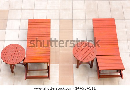 empty poolside deckchairs with beautiful blue swimming pool from top view