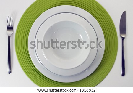 Empty porcelain plate with knife and fork on a green stylish cloth - stock photo