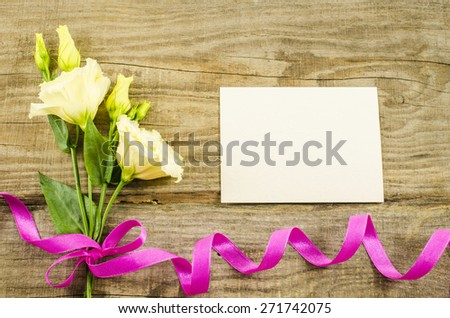 Empty postcard, colorful flowers and ribbon on wooden background - stock photo