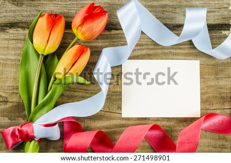Empty postcard with colorful flowers and ribbon on wooden background - stock photo