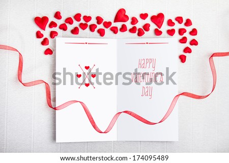 Empty postcard with Happy Valentine's Day typography and a red ribbon with fabric hearts on textured background. Valentine Day design.