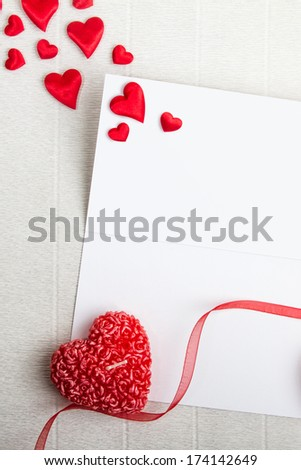 Empty postcard with heart-shaped candles, red ribbon and small fabric hearts scattered around. Valentine day design. - stock photo