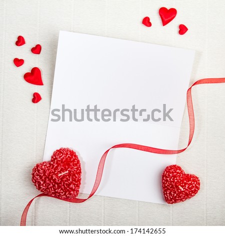 Empty postcard with heart-shaped candles, red ribbon and small fabric hearts scattered around. Valentine day design.