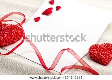 Empty postcard with heart-shaped candles, red ribbon and small fabric hearts. Valentine day design.