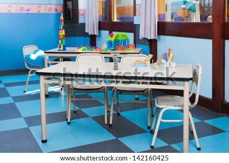 Empty preschool classroom with blocks and crafts on table - stock photo