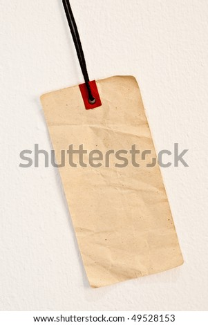Empty price tag on white painted wall - stock photo