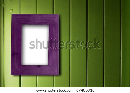 empty purple frame fixed on a green wooden wall, the color of the inner part of the frame is white - stock photo