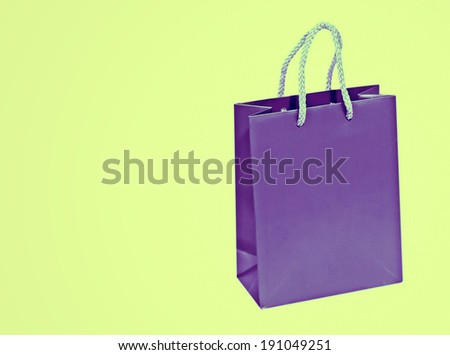 Empty purple shopping bag on green background.