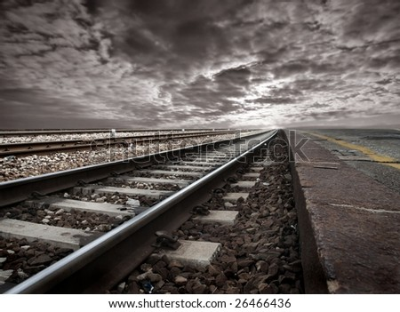 empty railway tracks in a stormy landscape - stock photo